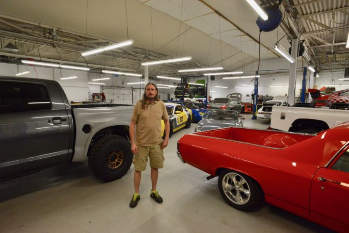 Dax Raub stands among the millions of dollars worth of cars, tools and experience in the 3R shop.