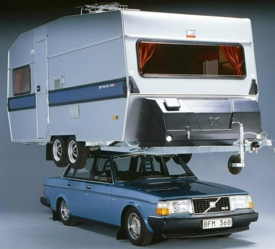 A tow-behind camper on a Volvo 240 roof